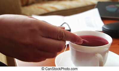 Woman pours tea for a business lunch. - Woman holding a...