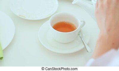 Woman pours tea into a cup
