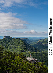 Woman Power Poses on Rocky Outcropping in Linville Gorge