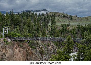 Woman Power Poses on Suspension Bridge Over Hellroaring Creek