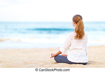 woman practices yoga and meditates in lotus position on beach