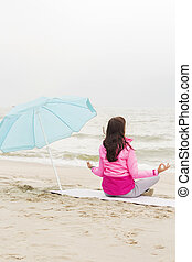 woman practices yoga and meditates in the lotus position on the beach