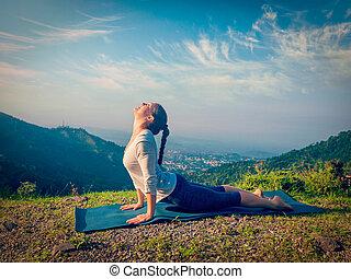Woman practices yoga asana Urdhva Mukha Svanasana outdoors -...