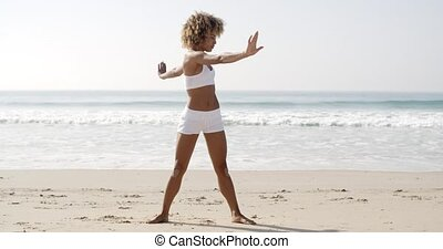 Woman Practices Yoga On A Beach - Slender fit young black...