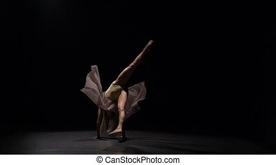 Woman practicing contemporary against black background of...