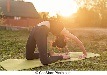 woman practicing outdoors meditating in yoga position.