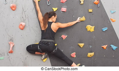 Woman practicing rock climbing on artificial wall indoors....