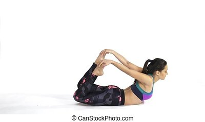 Woman practicing yoga Dhanurasana, a Bow Pose - Young...