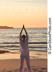 Woman practicing yoga during the sunset at the beach