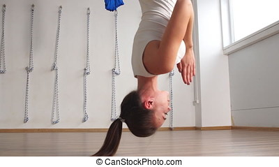 Woman practicing yoga fitness exercise in a white studio indoors.
