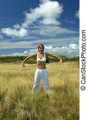 Woman practicing yoga in a field