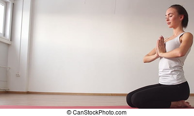 Woman practicing yoga in a studio indoors.