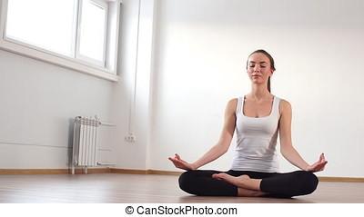 Woman practicing yoga in a studio indoors.