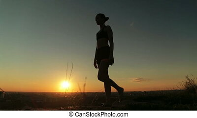 Woman practicing yoga in the park at sunset - lord of the dance pose