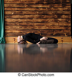 woman practicing yoga, lying in Reclining Hero exercise, Supta Virasana pose