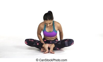 Woman practicing yoga Mulabandhasana, The Root Lock Pose -...