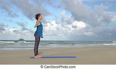 Woman practicing yoga on the beach at sunset. Exercises calmness and harmony.