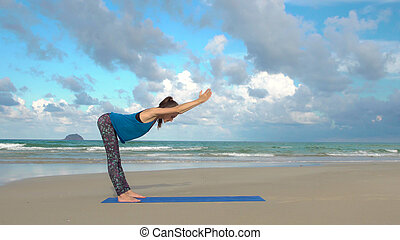 Woman practicing yoga on the beach at sunset. Healthy lifestyle. Exercises calmness and harmony