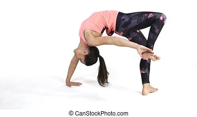 Woman practicing yoga One Leg Wheel Pose - Young attractive...