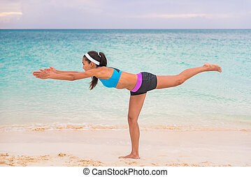 Woman practicing yoga outdoor on beach at sunset. Girl training doing Warrior III pose stretching standing on one leg for balance