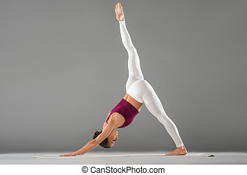 woman practicing yoga, standing in one legged downward...