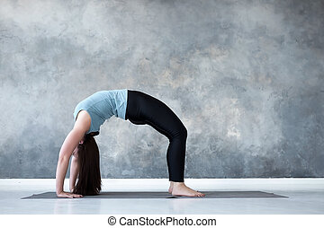 young woman practicing yoga standing in eagle exercise garudasana pose young attractive woman