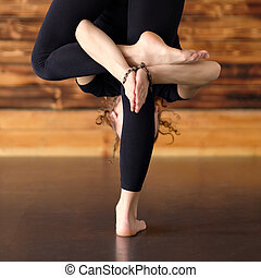 Woman practicing yoga, standing in uttanasana pose, forward bend