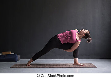 Woman practicing yoga Utthita parsvakonasana exercise, Extended Side Angle pose