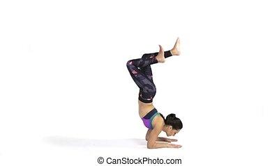 Woman practicing yoga Vrschikasana, Scorpion pose - Young...