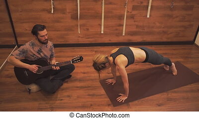 Woman practicing yoga while a man plays an acoustic guitar