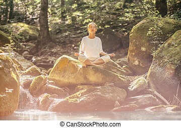 Woman practicing yoga with closed eyes outdoor.