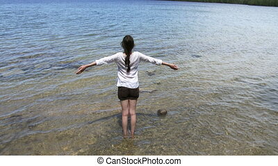 Woman practising yoga in a lake