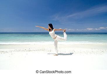 Woman practising Yoga (Warrior Position) on the beach.