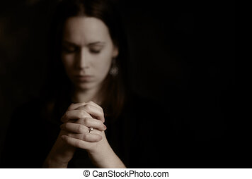 A brunette woman praying with her hands together