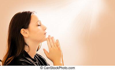 Woman Praying - A woman praying with light beams coming down