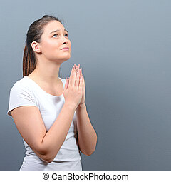 Woman praying about something or begging for mercy against gray background