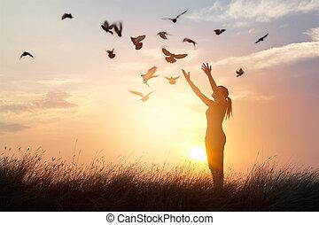 Woman praying and free bird enjoying nature on sunset ...