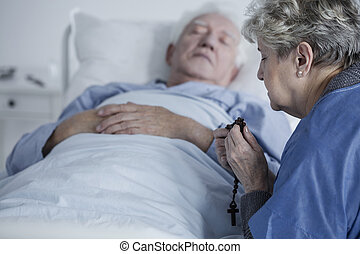 Elderly woman praying with rosary for the health of sick husband