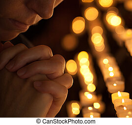 Woman praying in church cropped part of face and hands...