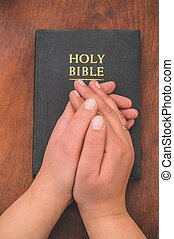 Woman praying on bible background. Hands folded in prayer concept for faith, spirituality and religion.