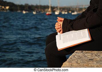 Woman praying on bible
