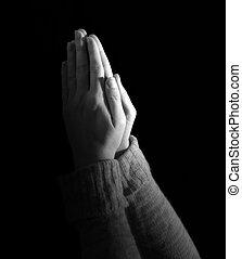 Woman praying on black background