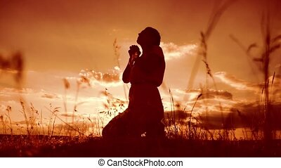 woman praying on her knees. Girl folded her hands in prayer silhouette at sunset. slow motion video. Girl folded her hands in prayer pray to God. the girl praying lifestyle asks forgiveness for sins of repentance. concept Christianity religion catholicism