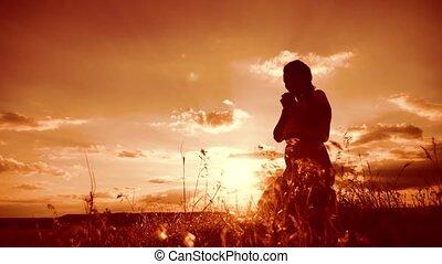 woman praying on her knees. Girl folded her hands in prayer...