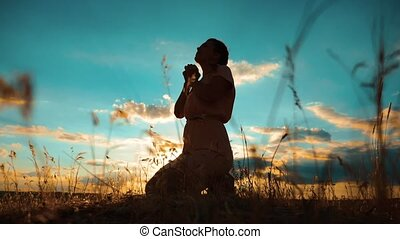 woman praying on her knees. Girl folded her hands in prayer silhouette at sunset. slow motion video. Girl folded her hands in prayer pray to God. the girl praying asks forgiveness for sins lifestyle of repentance. concept Christianity religion catholicism