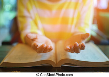 woman praying on holy bible in the morning. teenager hand with Bible praying, Hands folded in prayer on a Holy Bible in church concept for faith, spirituality and religion. victory concept for god.