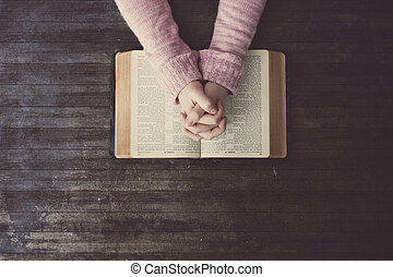 Woman praying on table - Woman praying over a Bible on a ...