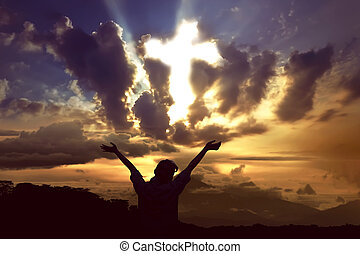 Woman praying to god with ray of light shaping cross on the sky