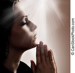 Woman Praying - Woman praying with lights shining down