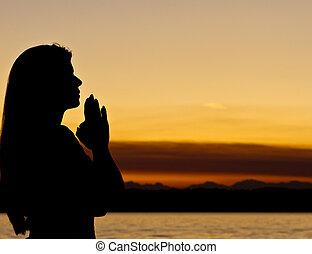 Faithful woman prays outdoors during sundown.